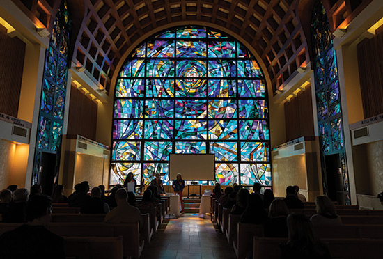 stain glass windows seen from inside the stauffer chapel as students worship