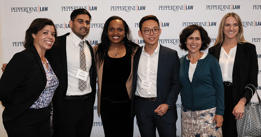 six people standing in front of white pepperdine law step and repeat sign