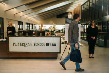 three people are pictured at the School of Law welcome desk