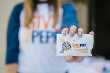 girl with blue nails holding out a give2pepp card