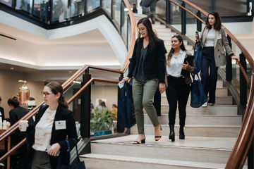 four female students in business casual walk down the stairs at Caruso law school