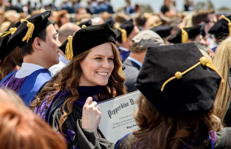 A female student proudly holds her Pepperdine diploma at graduation