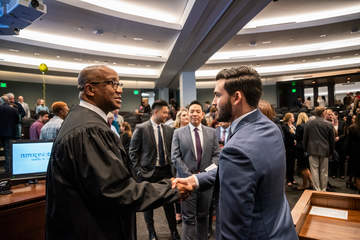 Judge Andre Birotte shaking the hand of a male student while a queue forms behind them in the auditorium