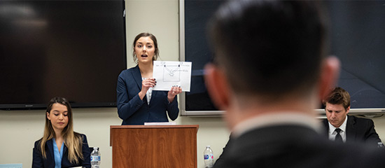 a female student presents her case holding a piece of paper up at a moot court competition