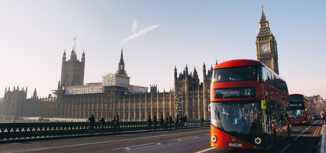 a red bus in London crossing a bridge with parliament in the background