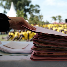 a stack of case files for inmates in a Uganda prison