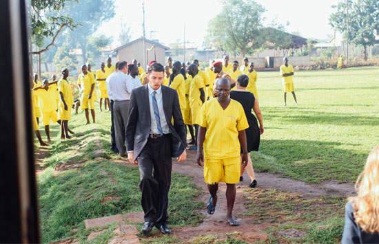 a lawyer walks with a man in a Ugandan prison