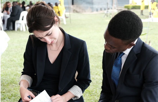 a male and female law student look over paperwork in a Uganda prison