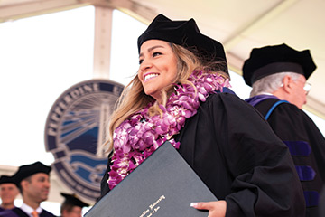 Female law graduate clutching her diploma wearing a flower lei