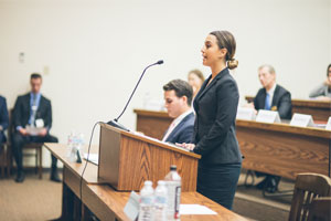 A female student standing up at a podium at a moot court competition