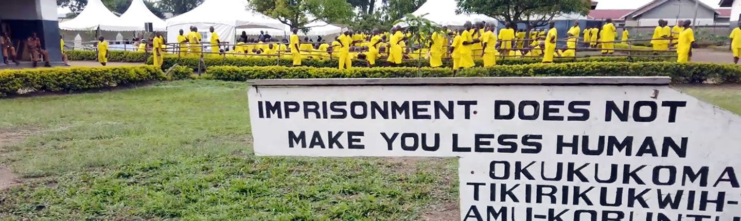 Sign from a Ugandan prison with inmates in the background