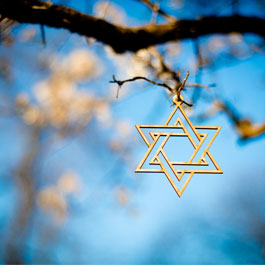 a Star of David hanging in front of a blue sky background