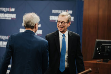 Paul Caron shakes a man's hand at the Straus Institute for Dispute Resolution