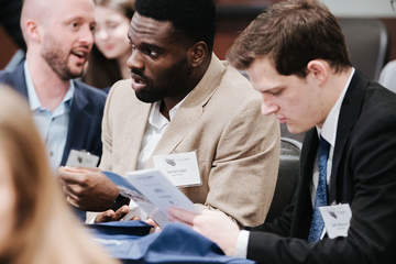 three male students looking over a brochure at a School of Law event