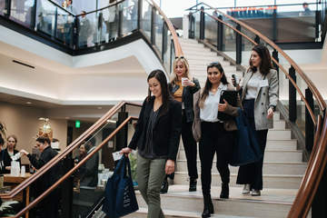 Four female JD students walk down the stairs in the atrium