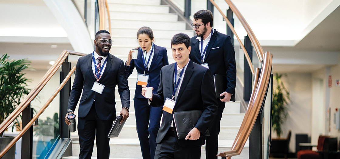 four law students descent the staircase dressed in suits