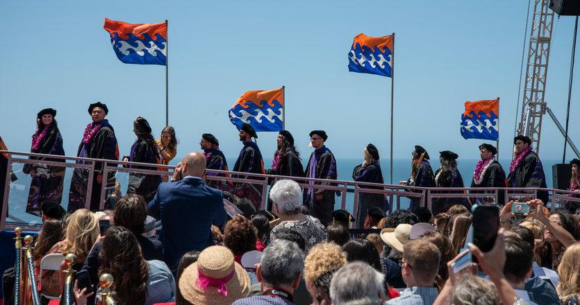 students waiting to cross the stage at graduation under the Pepperdine waves flag