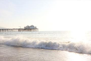 waves hitting the shore with the Malibu pier in the background