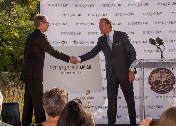 Rick Caruso shakes hands with Dean Paul Caron at a ceremony at the School of Law