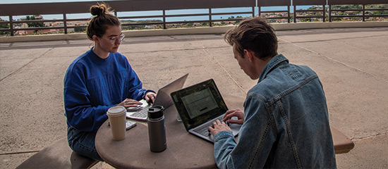 Two students on laptop computers sitting at table outside in malibu