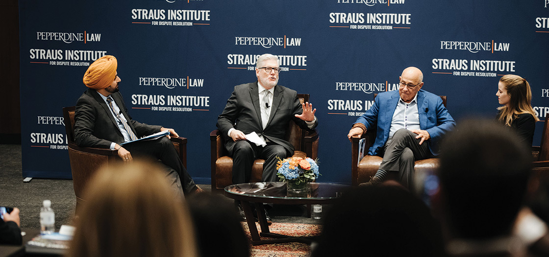 Four people sit and talk on a stage at a Staus Institute event