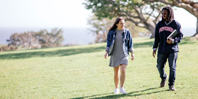 two students walk and talk across alumni park at Pepperdine