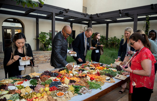 eight people pictured gathering around a giant charcuterie board at an event