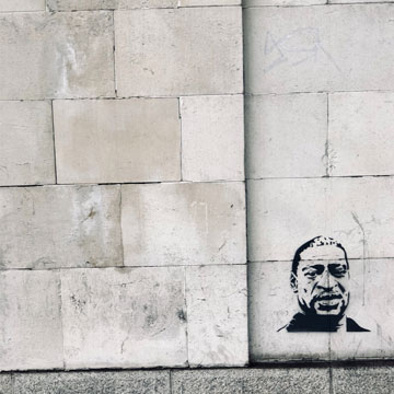 A  concrete wall with a spray-painted image of George Floyd
